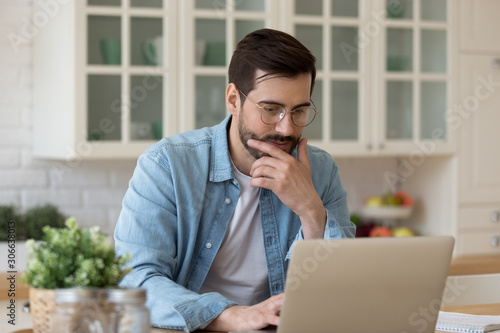 Young guy using laptop notebook sit at home table