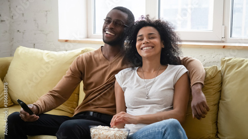 Fotografie, Obraz  Overjoyed biracial couple have fun watching TV together