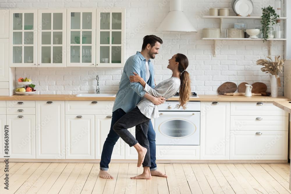 Obraz Happy romantic couple dancing in modern kitchen at home fototapeta, plakat