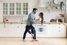 Happy Romantic Couple Dancing In Modern Kitchen At Home