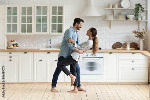 Obraz Happy romantic couple dancing in modern kitchen at home - fototapety do salonu