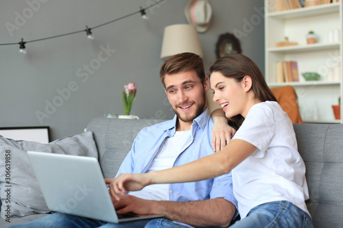 Tela Young couple doing some online shopping at home, using a laptop on the sofa