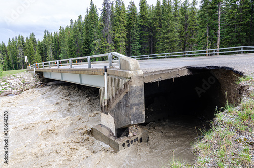 Photo erosion from flood waters take away road bridge