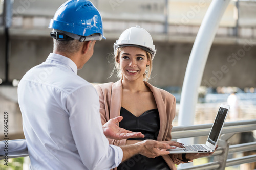 Young American beautiful female engineer with helmet dicsuss construction project with his manager by using laptop computer Wallpaper Mural