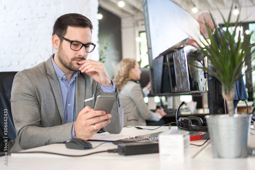 Fototapeta Handsome businessman is using a smartphone while working in office