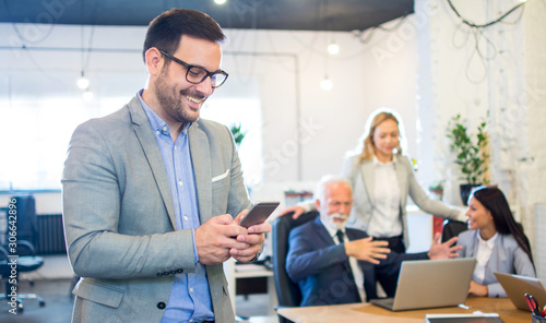 Smiling businessman using phone in the office with colleagues in the background.