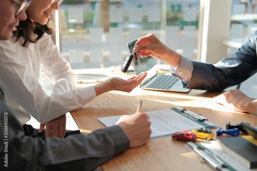 Photographie dealer salesman giving car key to owner