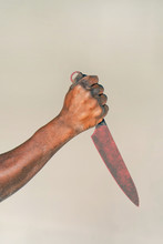 Hand Of African Man Holding A Knife Isolated On A Gray Background. African Man Hold Knife - Aggression. Big Kitchen Knife In Man Hand.