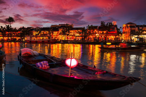 Papiers peints Grenat Traditional boats in front of ancient architecture in Hoi An, Vietnam.