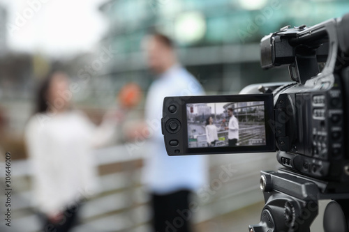 Young journalist interviewing man on city street, focus on camera display Wallpaper Mural