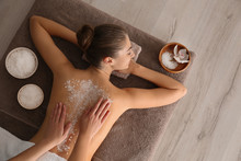 Young Woman Having Body Scrubbing Procedure With Sea Salt In Spa Salon, Top View