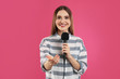 canvas print picture - Young female journalist with microphone on pink background