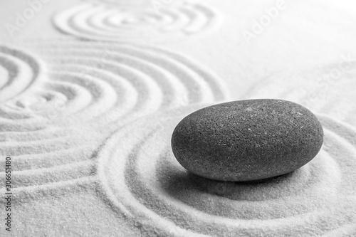 Fototapeta Piasek  grey-stone-on-sand-with-pattern-space-for-text-zen-meditation-harmony