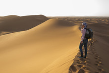Woman With Turban Watching The Dune Landscape In The Sahara Desert.
