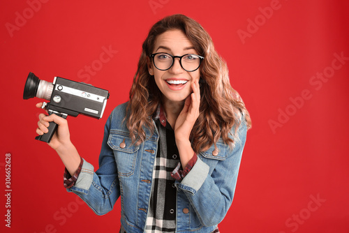 Fotografie, Obraz  Beautiful young woman with vintage video camera on red background