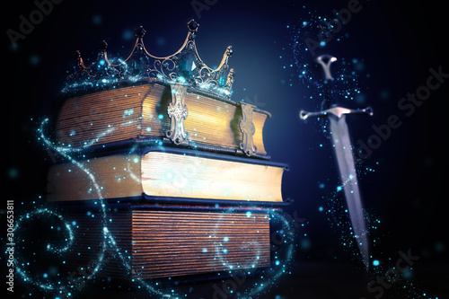low key image of beautiful queen/king crown over antique book and sword. fantasy medieval period. Selective focus