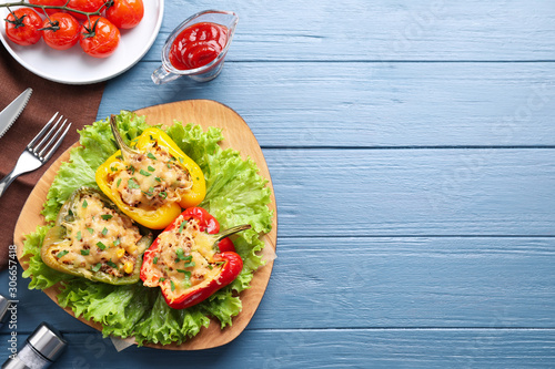 Fototapeta Tasty stuffed bell peppers served on blue wooden table, flat lay. Space for text obraz