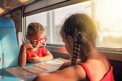 Little boy with his sister discussing their vacation during travelling by train Canvas Print