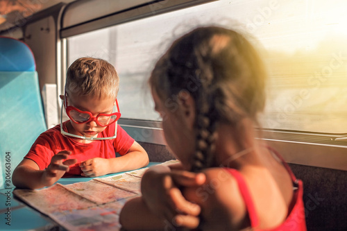 Little boy with his sister discussing their vacation during travelling by train Wallpaper Mural