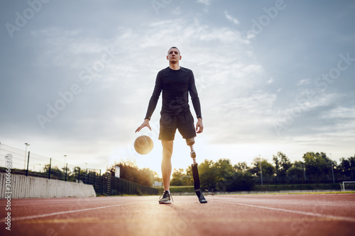 Full length of sporty caucasian handicapped man in sportswear and artificial leg dribble the ball while standing on racetrack Canvas Print