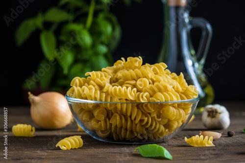 raw ingredients fusilli pasta in glass bowl onion fresh basil olive oil bottle g Canvas-taulu