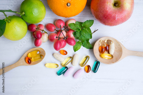 Fototapeta Multivitamin supplements from fruit on white wooden background obraz