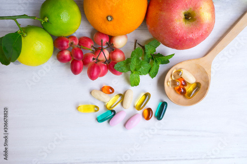 Fototapeta Multivitamin supplements from fruit on white wooden background obraz