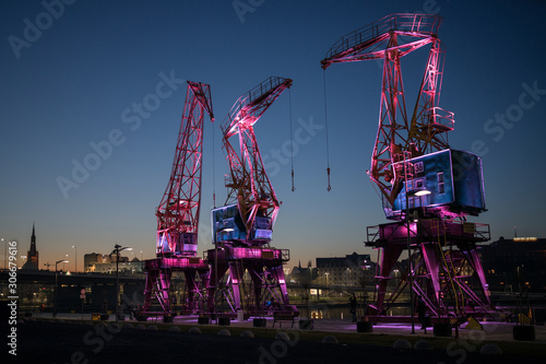 Obraz Dźwigozaury - Cranesaurs - colorfully illuminated cranes on the quay of Szczecin Łasztownia - fototapety do salonu