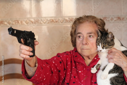 Fotomural Angry senior woman protecting her cat with a gun