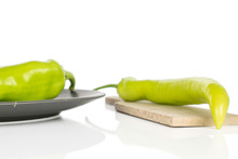 Group Of Two Whole Hot Green Pepper Banana On Gray Ceramic Plate On Wooden Cutting Board Isolated On White Background