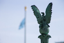Metallic Eagle On Foreground And Columbia University Flag Behind And Out Of Focus. New York City, Harlem