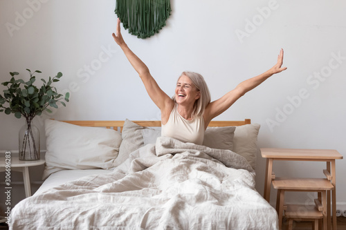 Obraz Aged female waking up in morning stretches seated in bed - fototapety do salonu