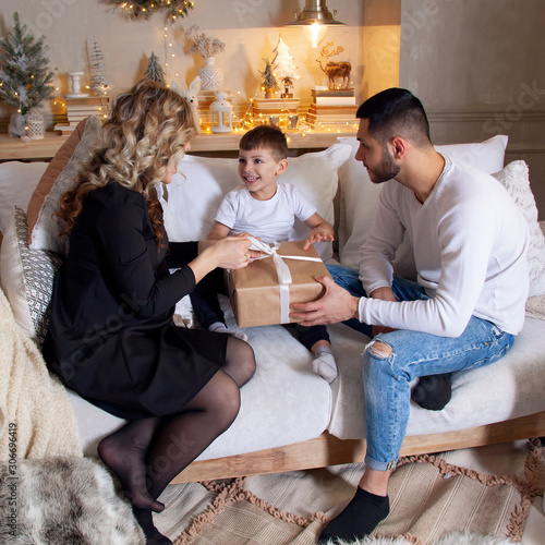Valokuva Young parents unwrapping presents with their little son.
