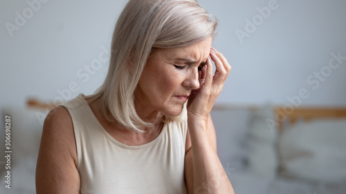 Fototapeta Closeup tired aged woman touches face with hand having migraine
