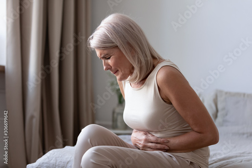 Fotografia Old unhealthy woman suffers from severe ache abdominal pain