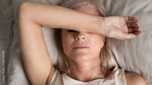 Photo Closeup melancholic woman lying put hand on face feels unwell