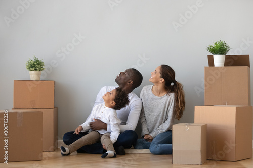 Happy mixed race family sitting on floor between cardboard boxes.