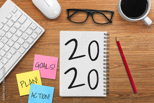 Photo  New Year Resolution Goal List 2020 - Business office desk with notebook written in handwriting about plan listing of new year goals and resolutions setting