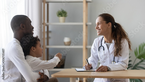 Happy african american man visiting friendly female pediatrician with son Wallpaper Mural