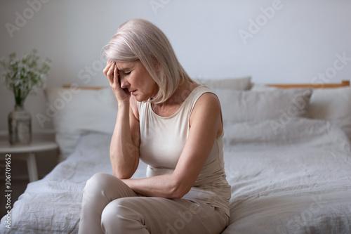Vászonkép Aged woman feels unwell suffers from barometric pressure headache