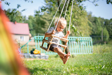 Little Boy Playing On Swing In...