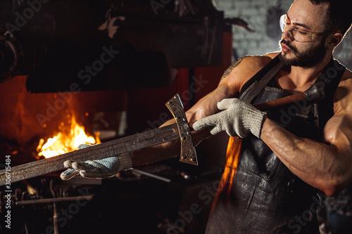 Fényképezés young bearded forger man studying handmade metal in workshop near furnace, weari