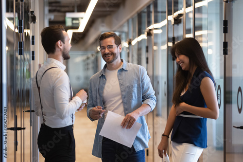 Photo Friendly diverse office workers standing in hallway chatting during break