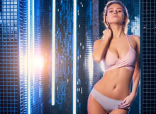 Attractive And Slim Woman In Underwear Stand Posing And Taking Shower Isolated In Cabin, Blue Colors. Freshness