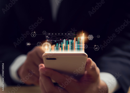 Stampa su Tela Stock exchange market concept, hand trader holding smartphone with graphs analysis candle line on bokeh colors light in night