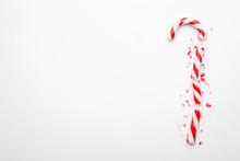 Broken Christmas Candy Cane On White Background. Minimal Composition With Peppermint Candy. Top View