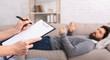 Leinwandbild Motiv Psychotherapist taking notes, listening to lying on couch patient