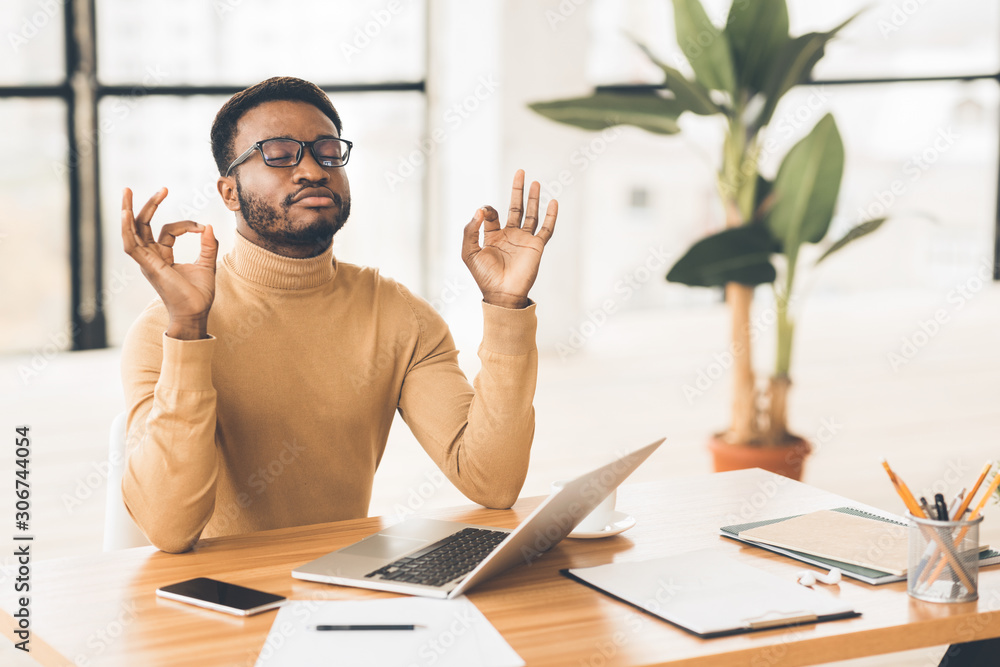 Fototapeta Black man meditating in office coping with stress
