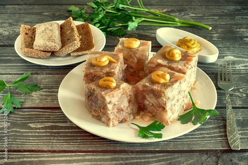 Photo aspic with mustard, bread  and parsley on a dark wooden background