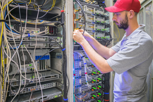 Fotografía  Network engineer switches power cables in the server room rack